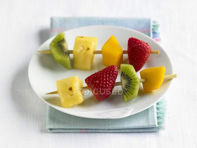 Фруктовые кебабы на белой тарелке — стоковое фото