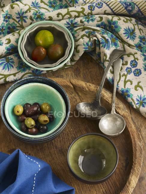 Varios platos de aceitunas y tomates sobre superficie de madera con toalla - foto de stock
