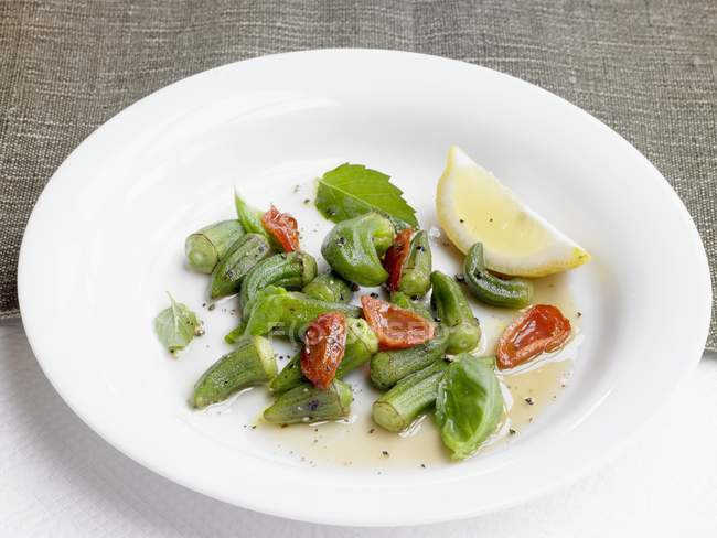 Un medley okra con pomodorini su piatto bianco — Foto stock