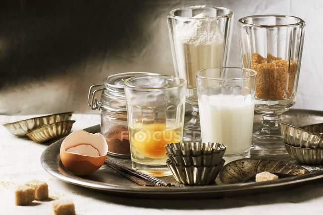 Varios ingredientes para hornear en vasos incluyendo harina, huevo, azúcar, leche y latas de la torta antigua en bandeja - foto de stock