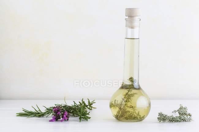 Óleo de ervas com alecrim, tomilho e lavanda em um frasco de vidro — Fotografia de Stock