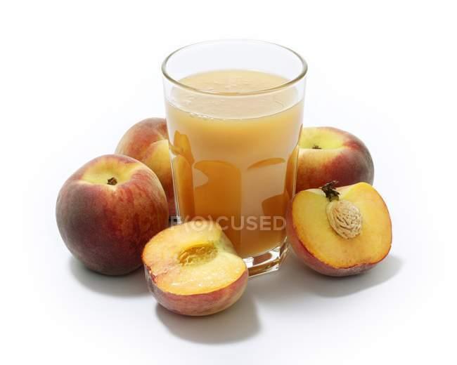 Vaso de zumo de melocotón y melocotones frescos - foto de stock