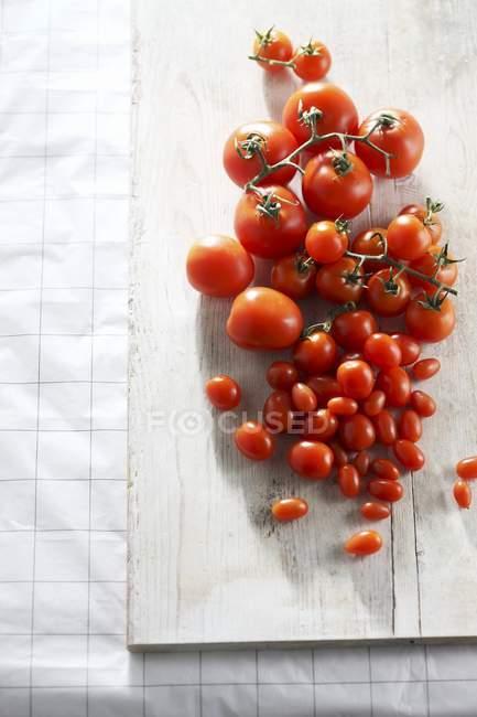 Varios tomates en tablero de madera - foto de stock