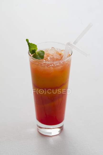 Closeup view of fruity drink with ice cubes and mint — Stock Photo
