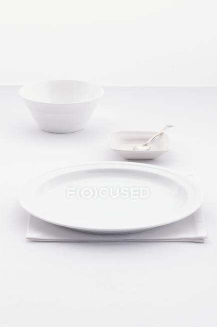 Closeup view of an white place setting with bowls, a plate, a spoon and a folded napkin — Stock Photo