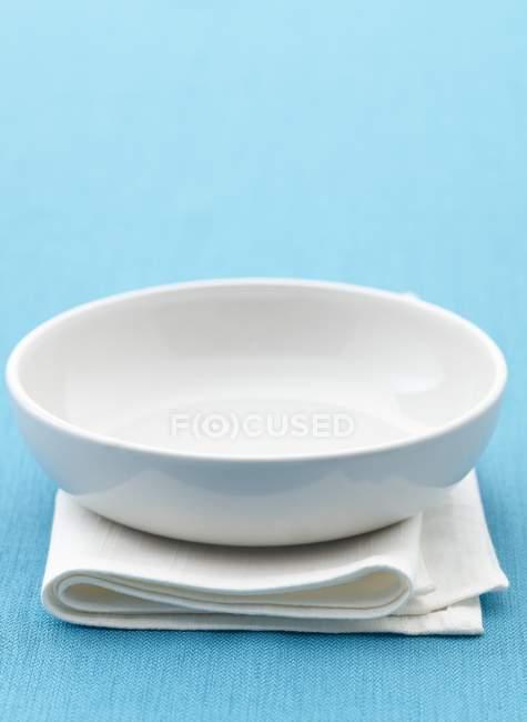 Vista de cerca de un plato blanco una toalla doblada y superficie azul - foto de stock