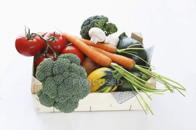 Una caja de verduras ecológicas sobre fondo blanco - foto de stock