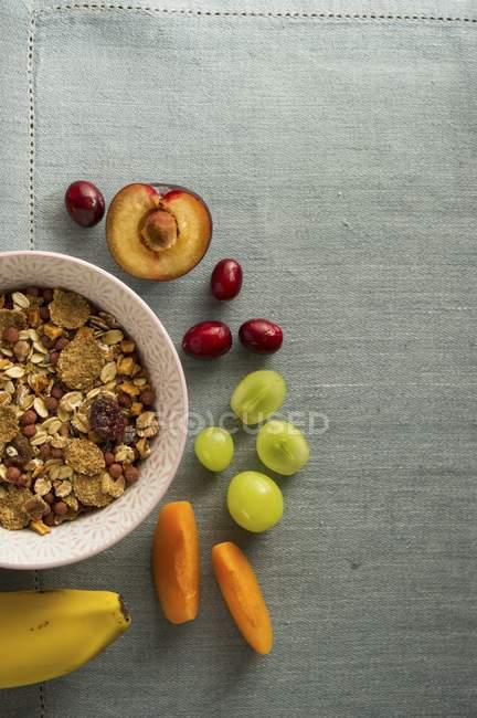 Cuenco de muesli junto a frutas frescas - foto de stock