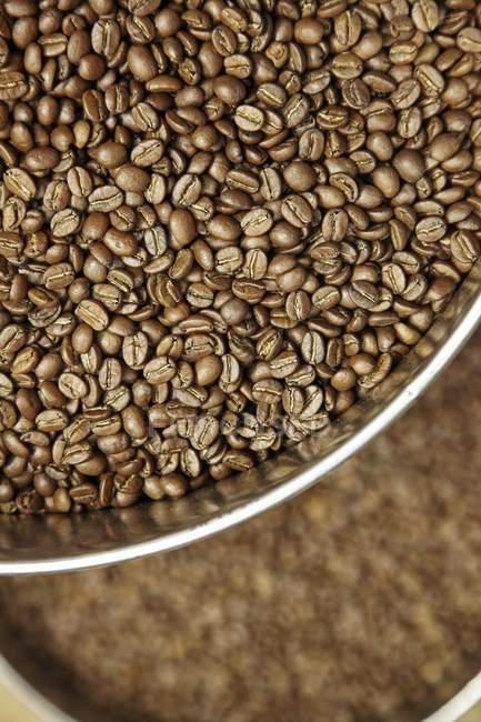 Granos de café en platos de metal - foto de stock
