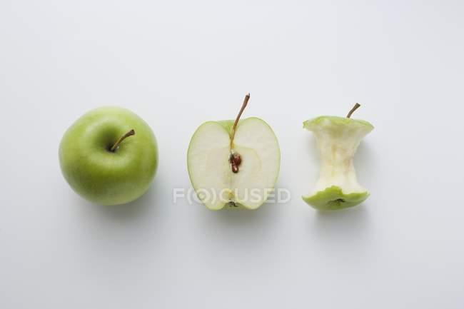 Manzana fresca entera y cortada a la mitad - foto de stock