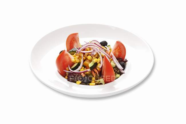 Corn salad with tomatoes and onions  on white plate — Stock Photo