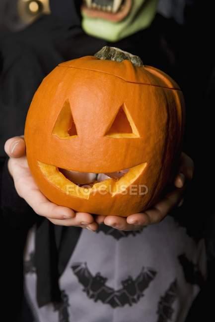 Enfant tenant citrouille d'Halloween — Photo de stock
