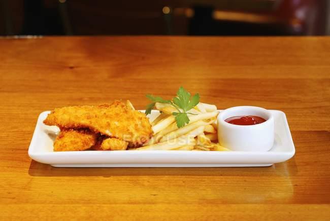 Крупным планом вид куриные пальчики и картофель фри с кетчупом — стоковое фото