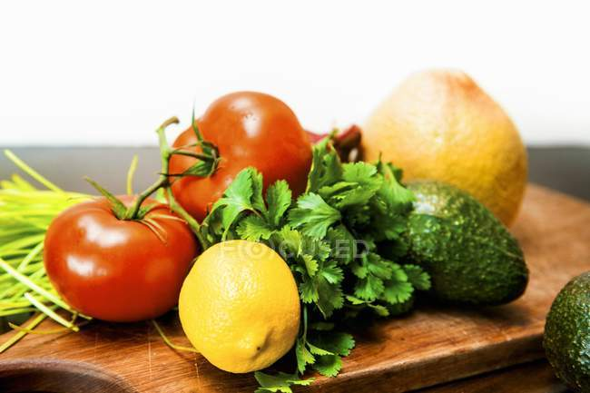 Fresh Produce on a Cutting Board over white background — Stock Photo