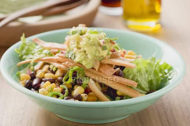 Крупный план салата с фасолью, кукурузой, полосками тортильи и гуакамоле в зеленой чаше — стоковое фото