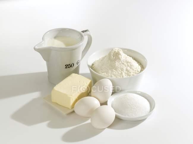 Vista elevada de mantequilla con huevos, azúcar, harina y leche - foto de stock