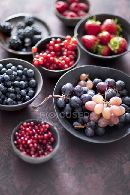 Berries and grapes in bowls — Stock Photo
