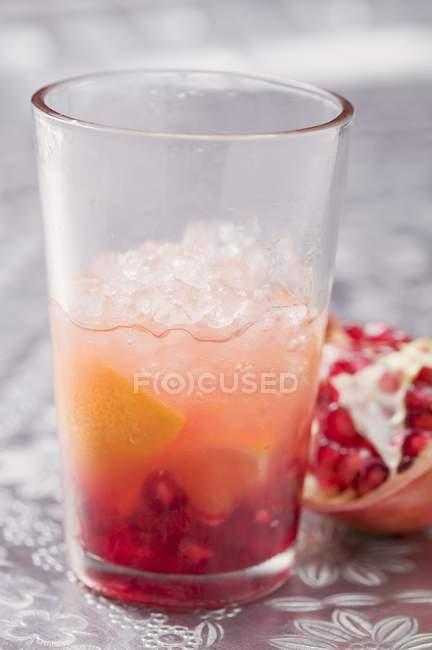Крупный план фруктового напитка с апельсином и гранатом — стоковое фото