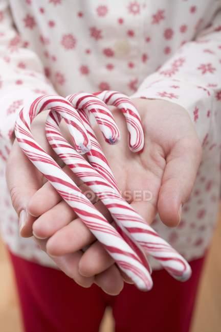Mulher segurando bastões de doces — Fotografia de Stock