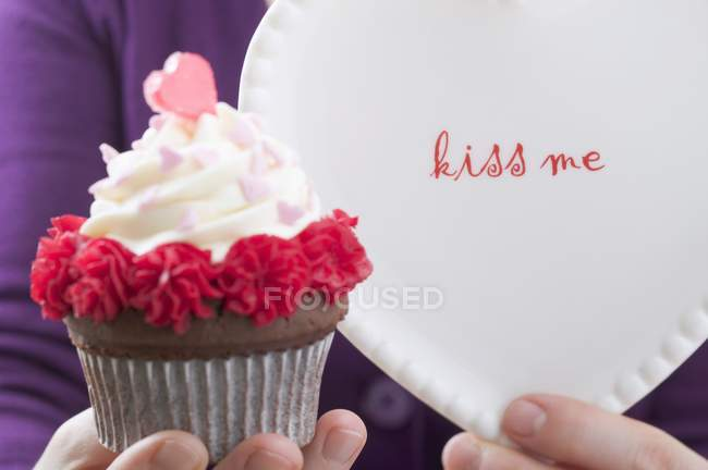 Female hand holding Valentines Day cupcake — Stock Photo