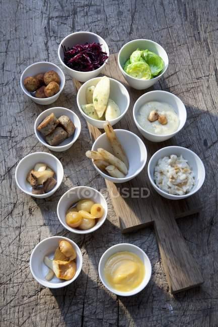 Vista elevada de varios platos con verduras, salsas y ensaladas - foto de stock