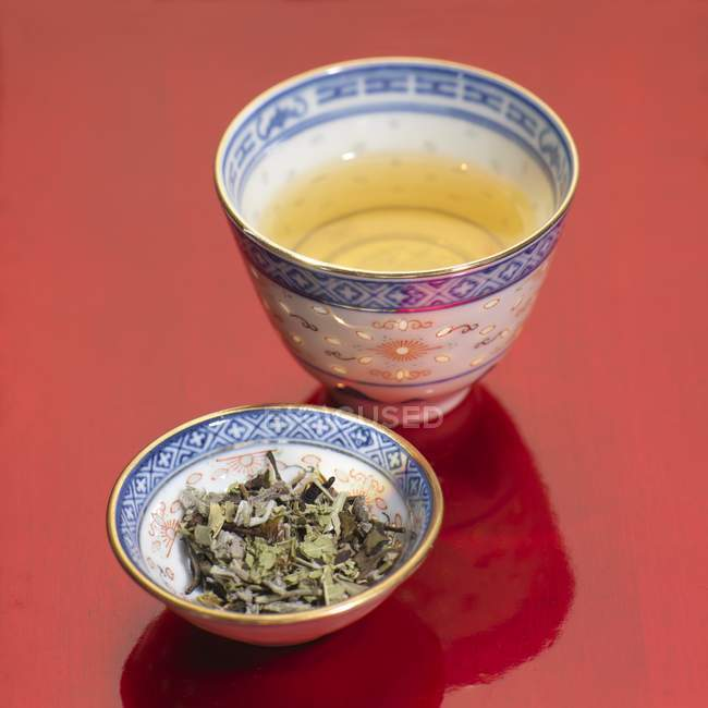 Green tea in bowl and tea leaves — Stock Photo