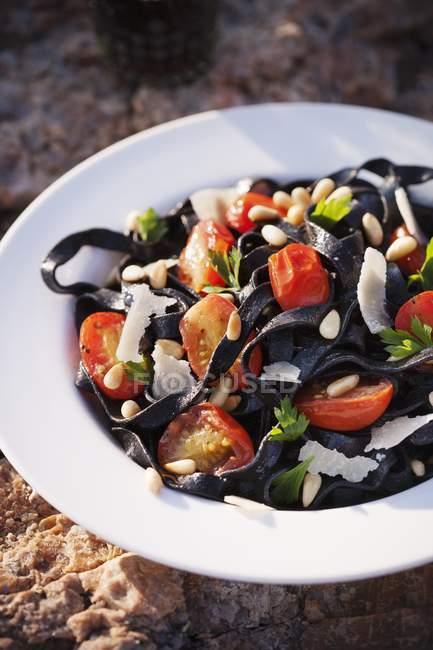 Squid ink pasta with cherry tomatoes — Stock Photo