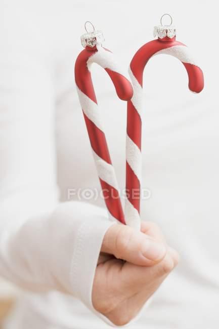 Main tenant des cannes à bonbons — Photo de stock