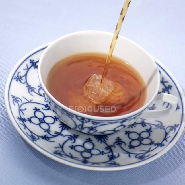Coulée de thé dans une tasse à motifs — Photo de stock