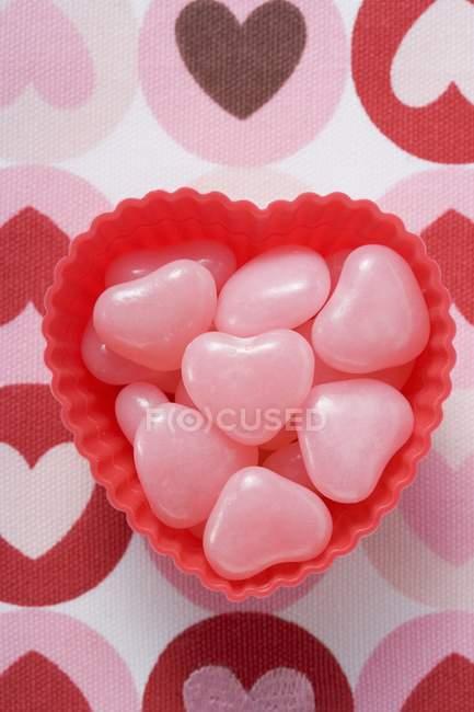 Вид зверху крупним планом рожеві формі серця цукерки в мисці — стокове фото
