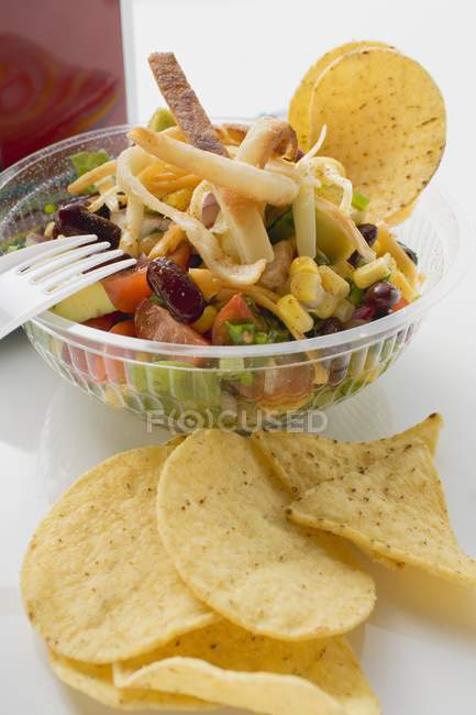 Mexican salad with tortilla chips to take away  over white surface — Stock Photo