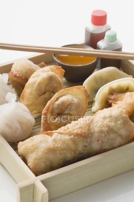 Closeup vista de aperitivos asiáticos no prato, com molhos e palitos — Fotografia de Stock