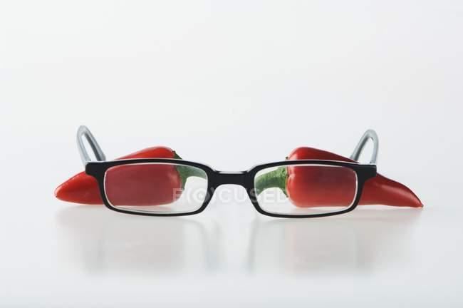 Piments rouges avec une paire de lunettes — Photo de stock