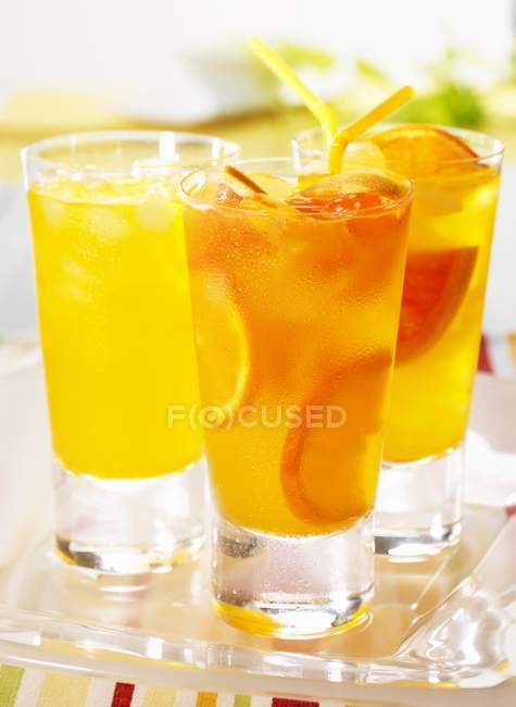 Closeup view of three tangerine and grapefruit drinks — Stock Photo