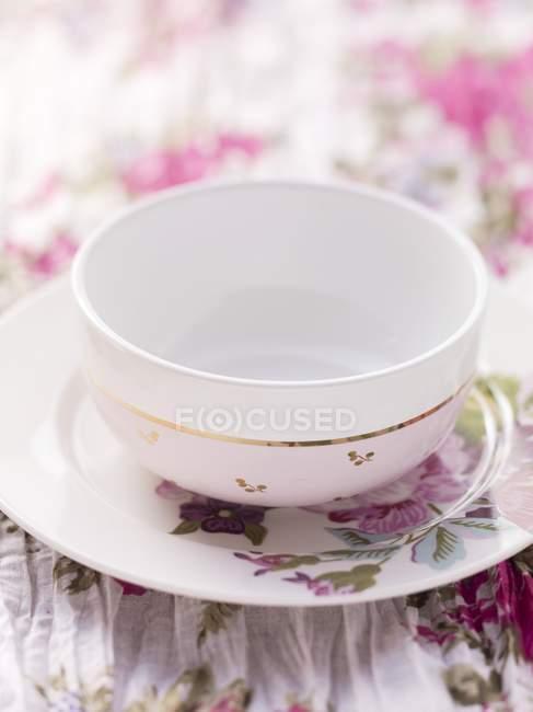 Vista de cerca de una placa con motivos florales y un tazón de fuente blanco en un paño de mesa florales - foto de stock
