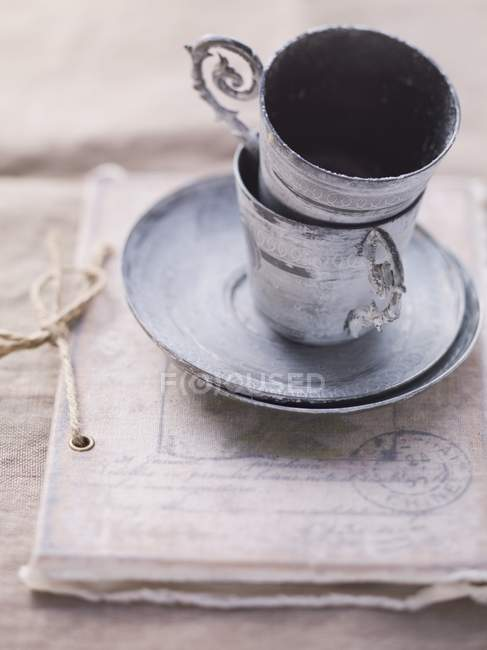 Closeup view of piled vintage cups and saucers on an old document — Stock Photo