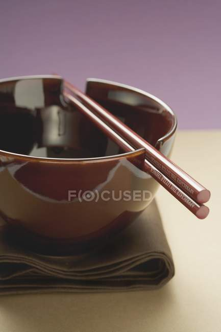 Closeup view of lacquer bowl with chopsticks on brown cloth — Stock Photo