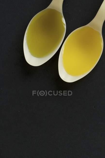 Primo piano vista dall'alto dell'olio di colza e olio di canapa in cucchiai su priorità bassa nera — Foto stock