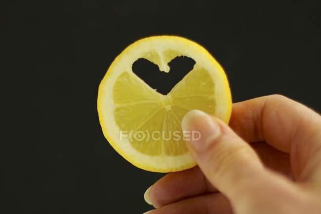 Женские руки, держащей ломтик лимона — стоковое фото