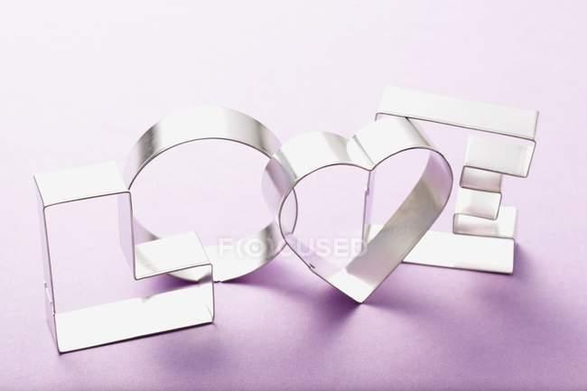 Vista de cerca de los cortadores de galletas formando palabra Amor en la superficie púrpura - foto de stock