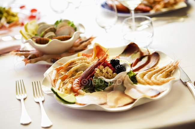 Closeup view of mixed starters with prawns, langoustines and carpaccio of tuna and of swordfish — Stock Photo