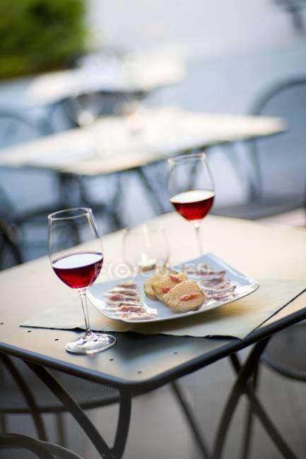 Einen Aperitif Rotwein, Brot und Schinken am Tisch im Café im freien — Stockfoto