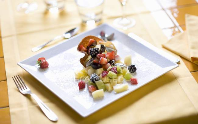 Closeup view of fresh fruit salad in crispy wafer on square plate — Stock Photo
