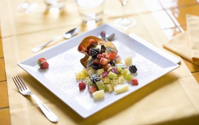 Vista del primo piano dell'insalata di frutta fresca in cialda croccante su piastra quadrata — Foto stock