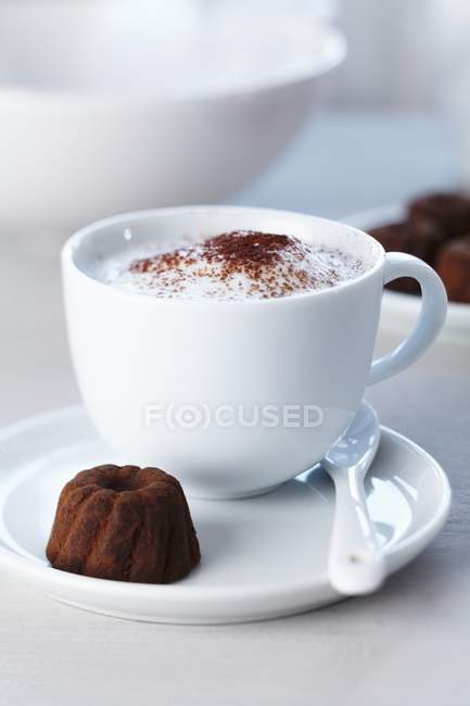 Cup of cappuccino and praline — Stock Photo