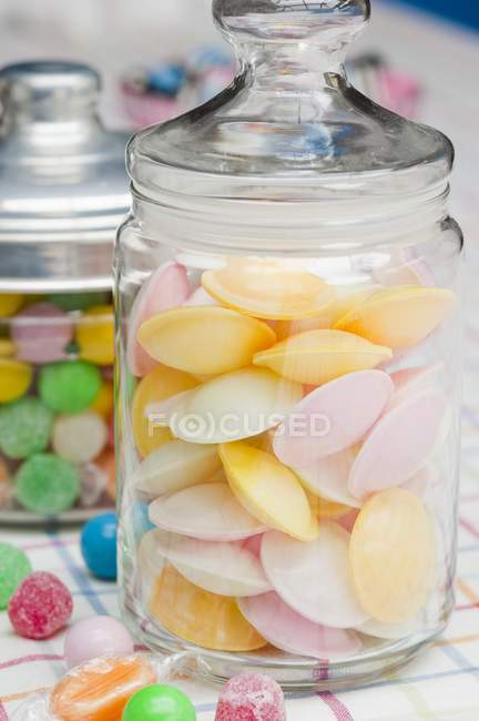Closeup view of flying saucers and colored sweets in glass jars — Stock Photo
