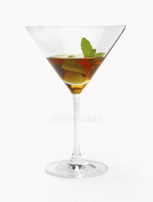 An alcoholic drink with olives and mint on white background — Stock Photo