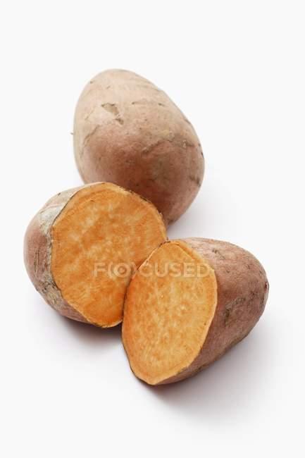 Ganze und halbierte Süßkartoffeln — Stockfoto