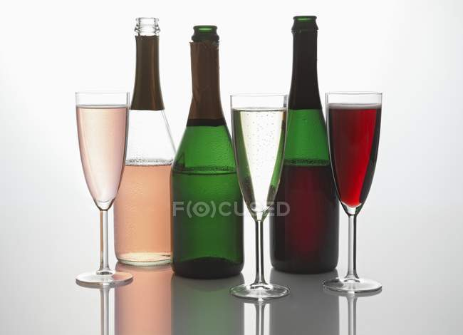 Sparkling wine bottles and glasses — Stock Photo