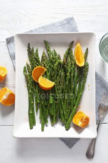 Espárragos verdes con naranjas - foto de stock